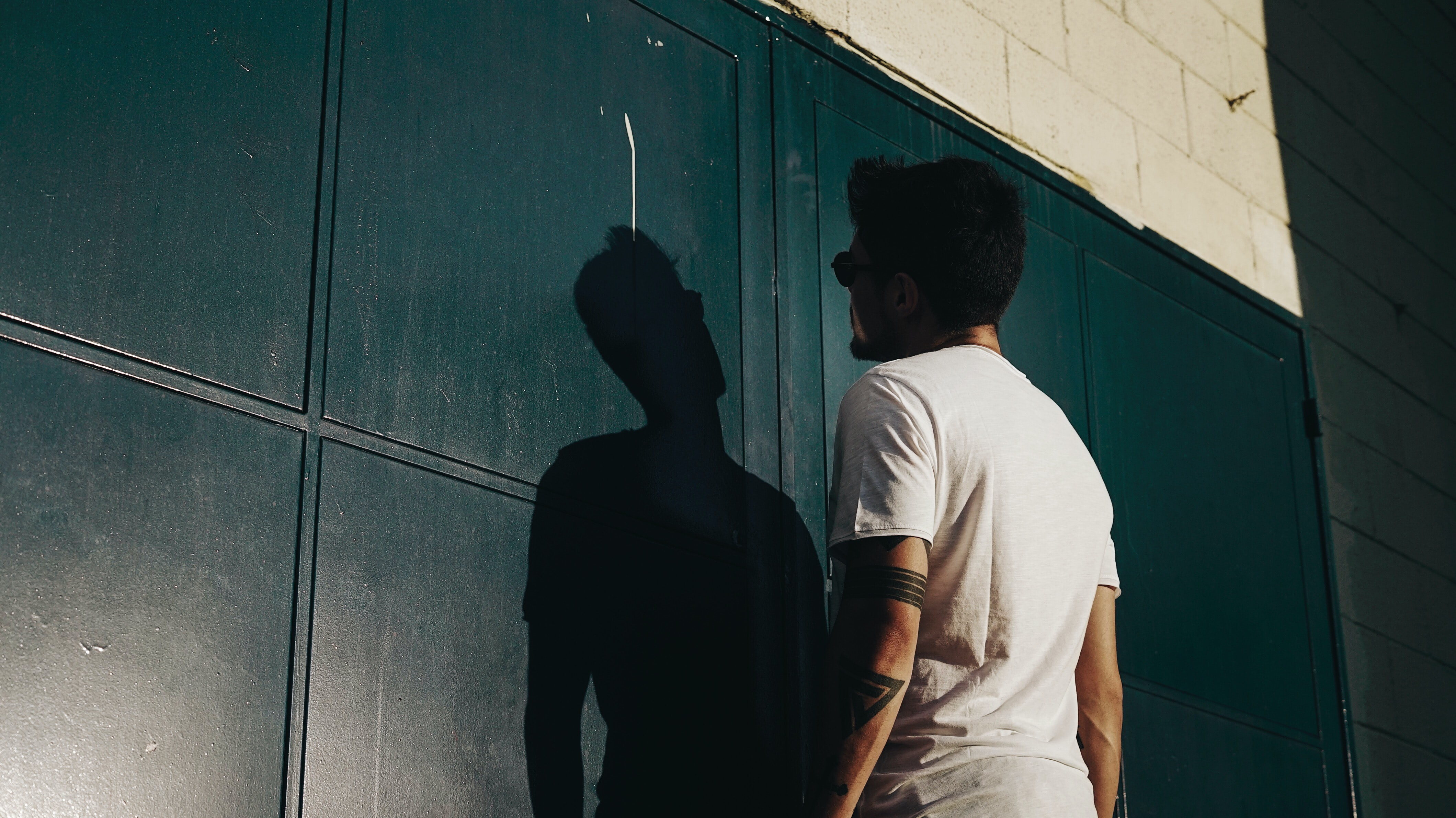 man in white t-shirt standing in front of wall