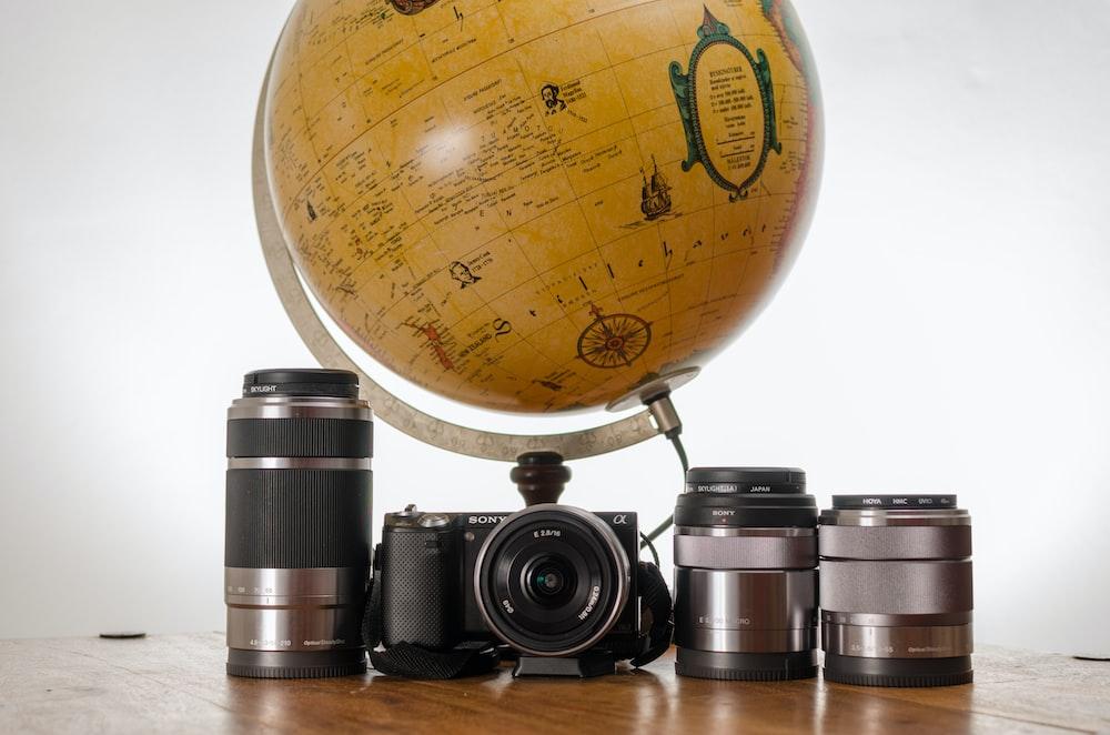 black SLR camera near brown desk globe