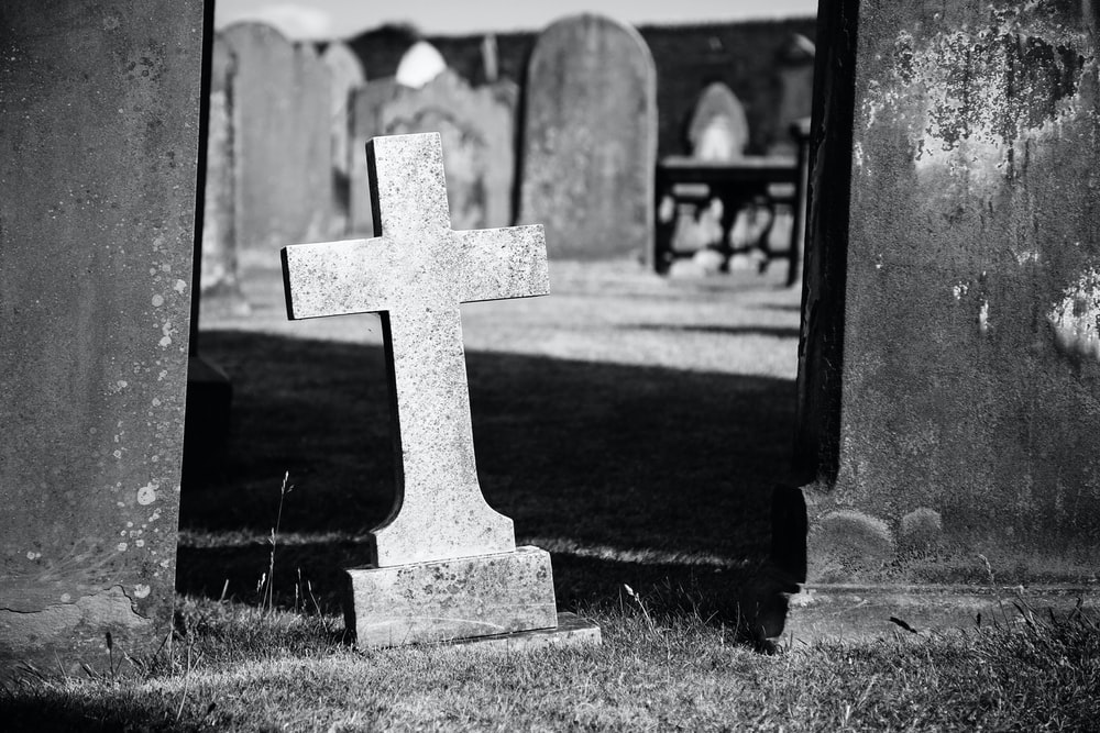 grayscale photo of gray graveyard cross
