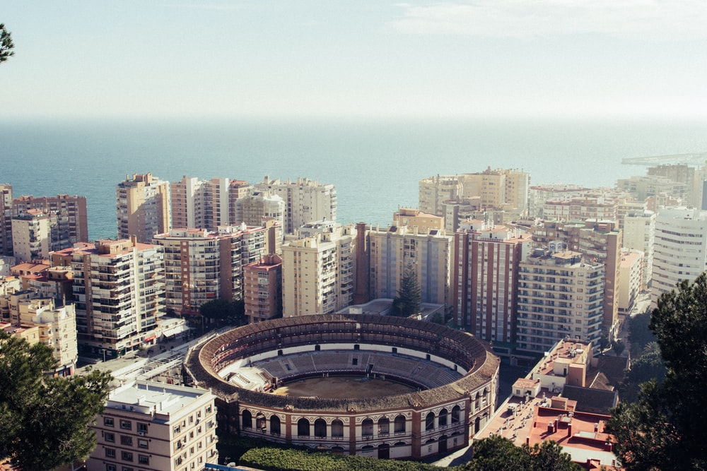 round stadium surrounded by buildings near the sea