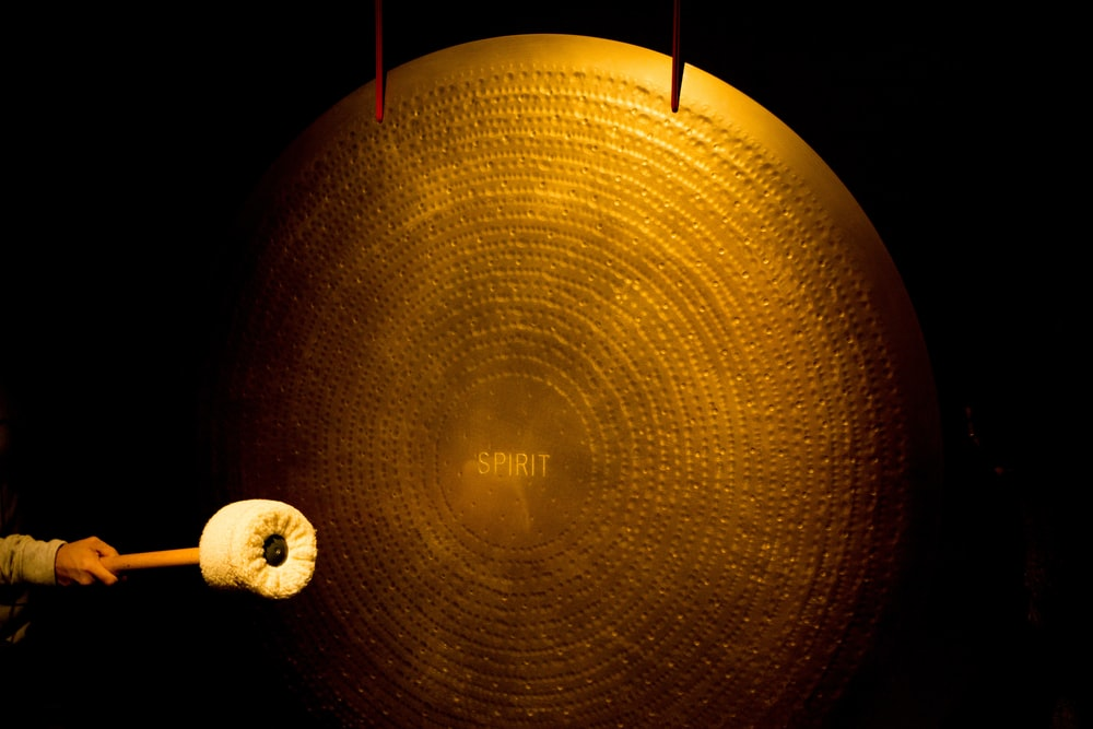 person striking large brass cymbal
