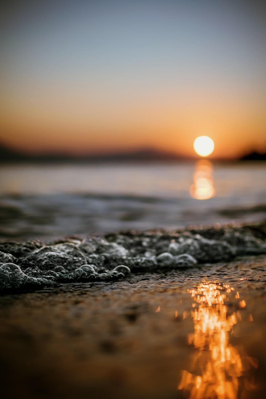 bokeh photography of splash of wave on seashore