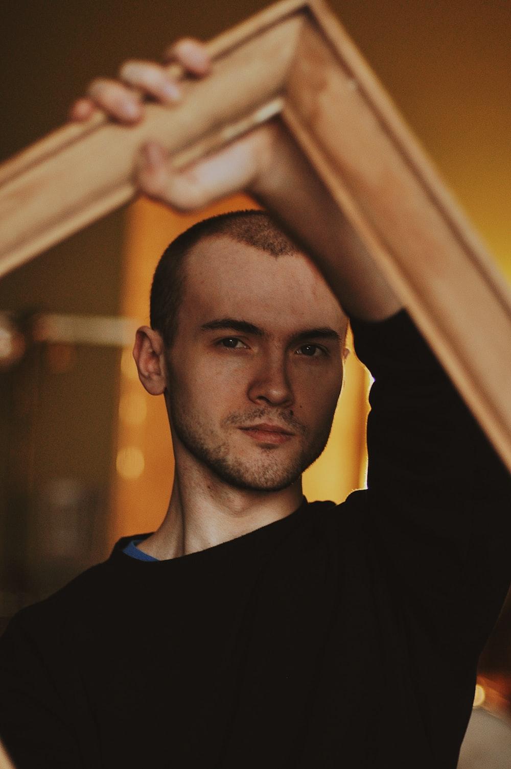 man holding wooden frame
