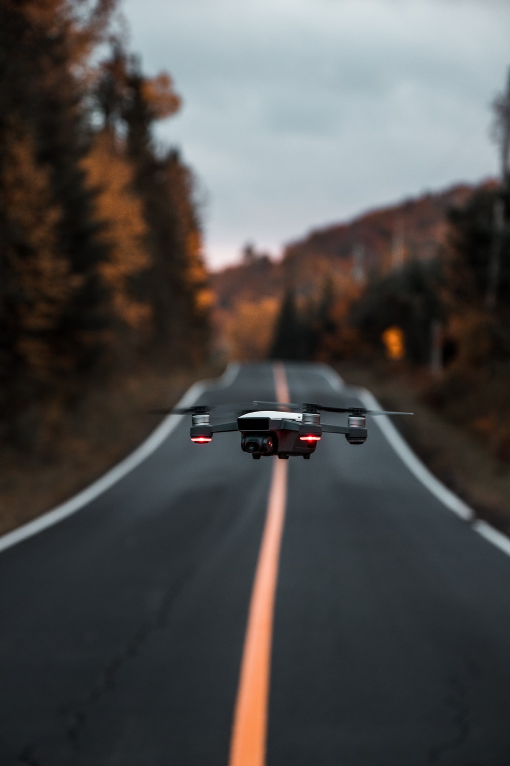 black and red drone in the middle of road near trees