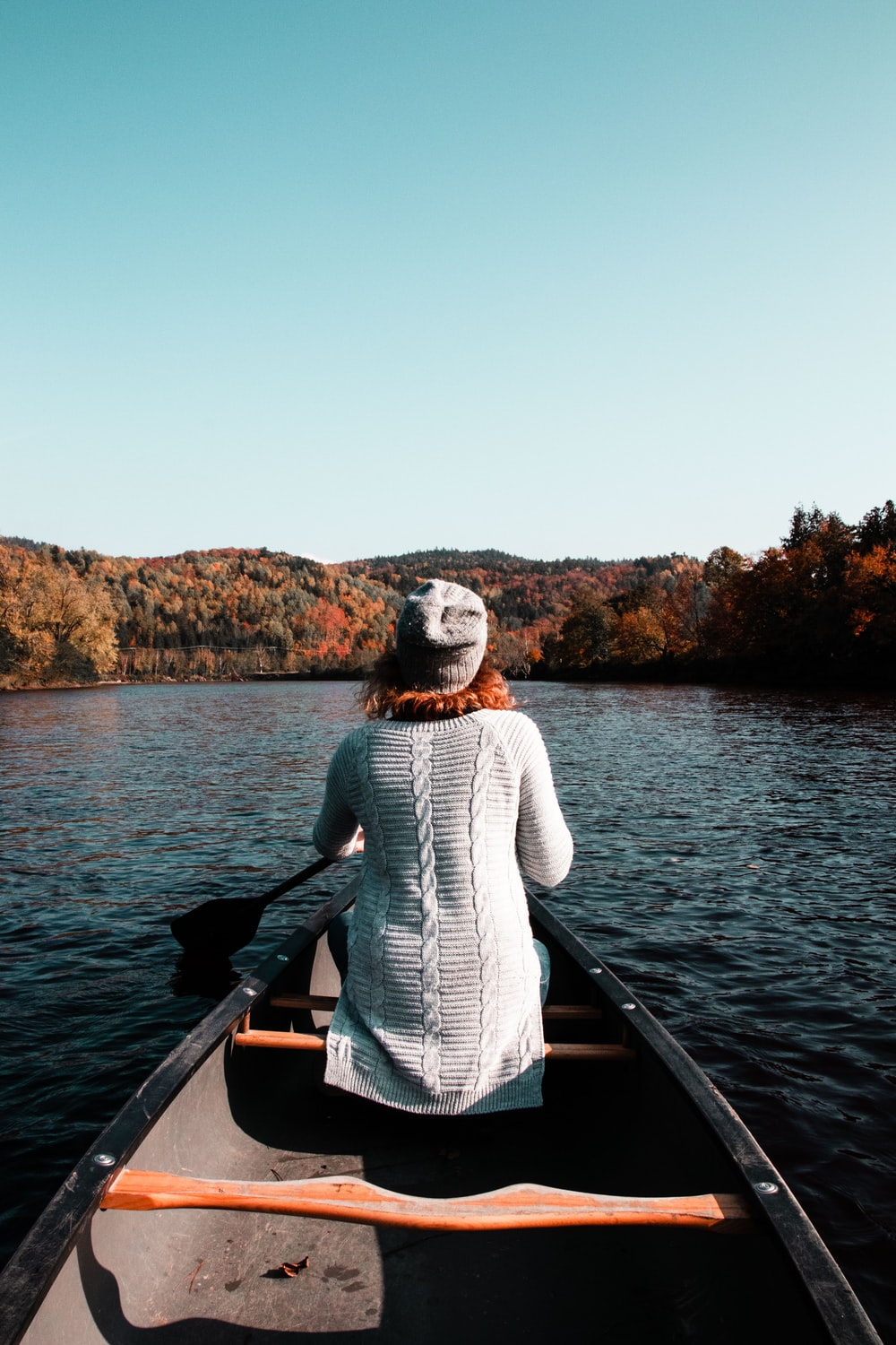 woman sitting on boat while paddling