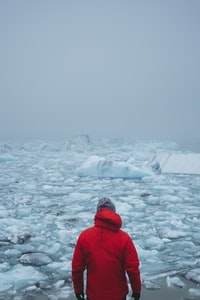 man in red coat standing in front of floating ice