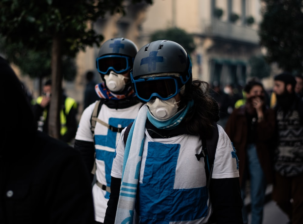 two persons wearing gas masks and helmets