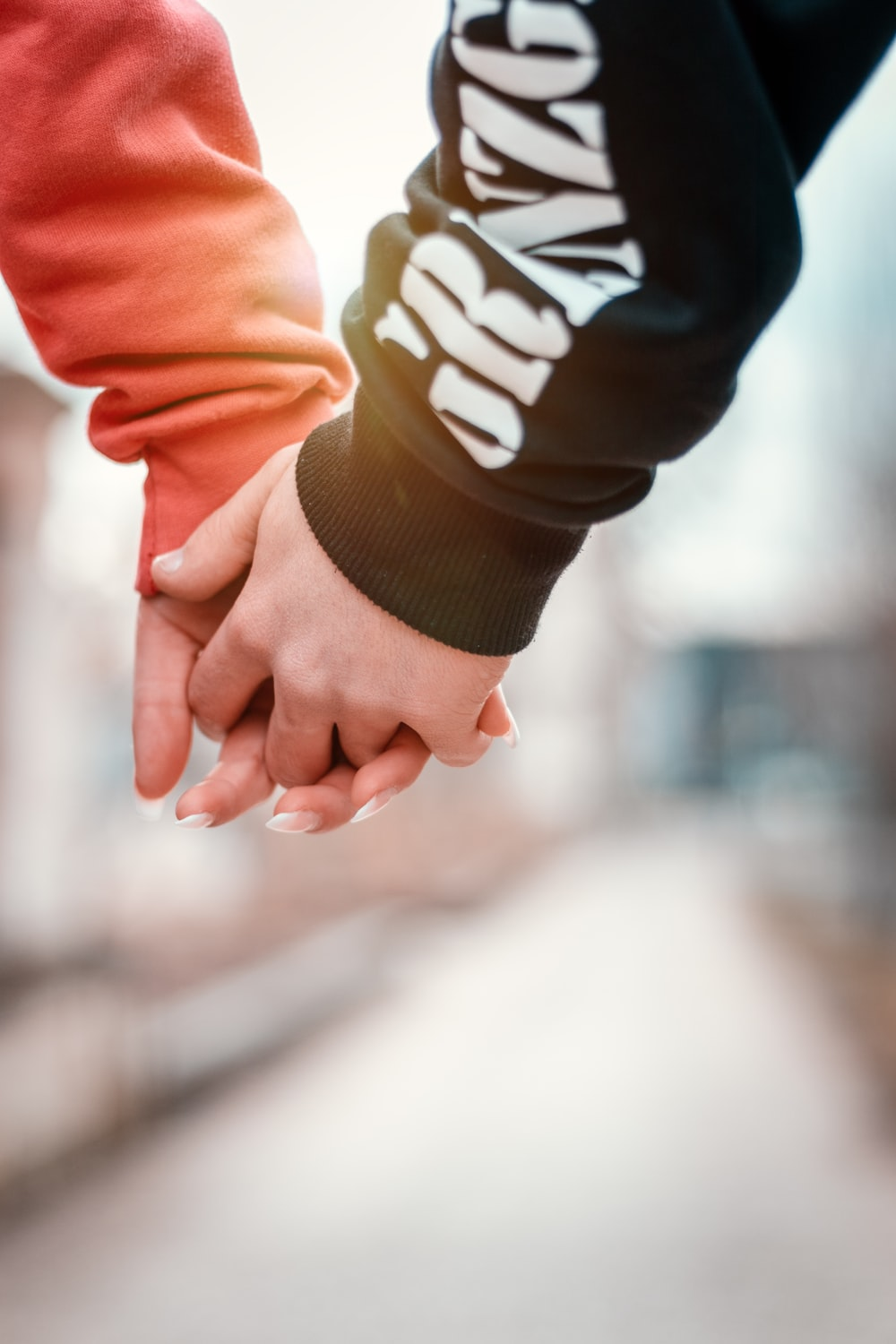two person holding hands in selective focus photography