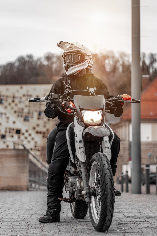 man riding motorcycle parking near pole