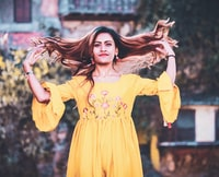 woman in yellow scoop-neck elbow-sleeved blouse playing with her hair during daytime
