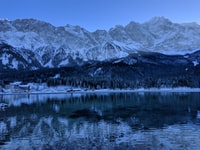 lake in front of snow capped mountains