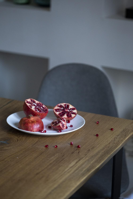 pomegranate fruit sliced into half on white plate