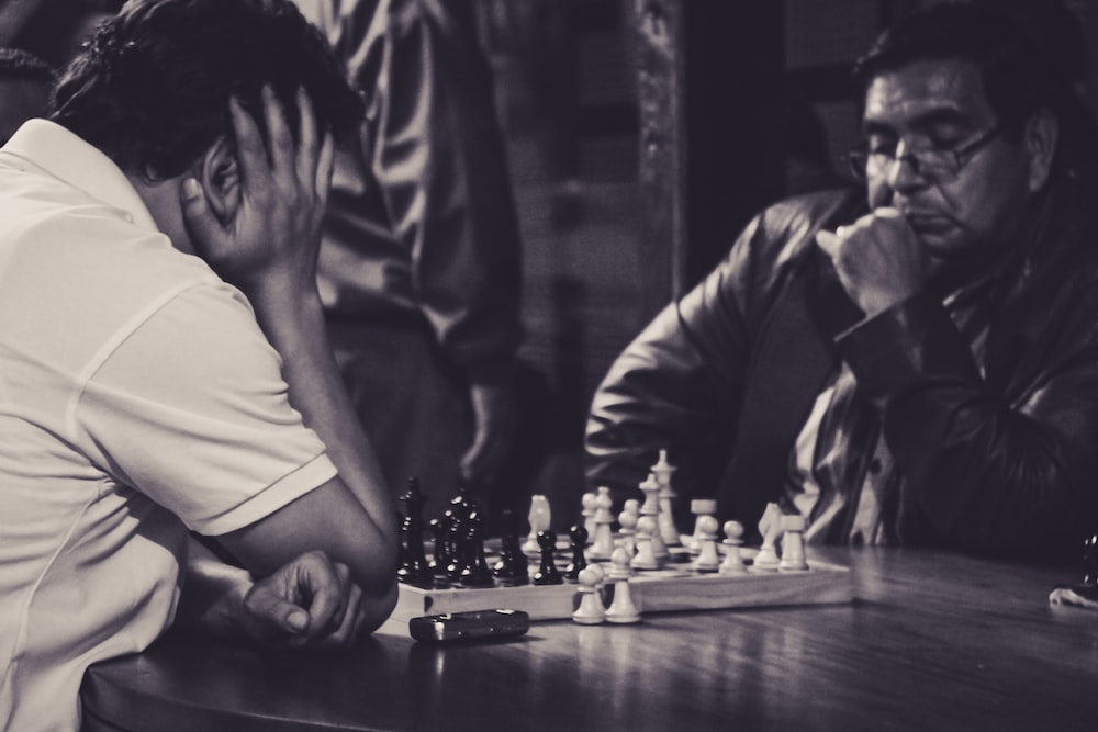 two men playing chess grayscale photo