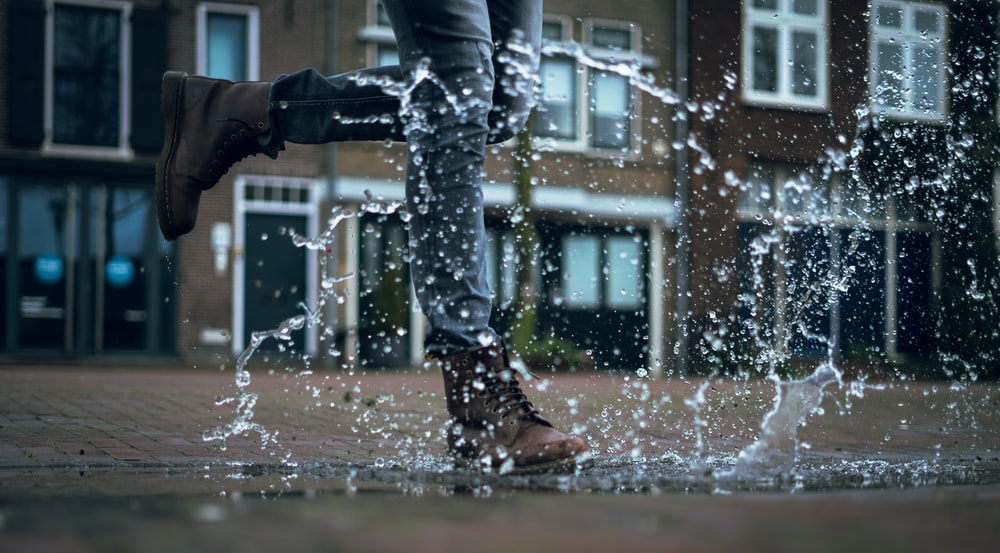 person in gray jeans and brown boots walking on water puddle