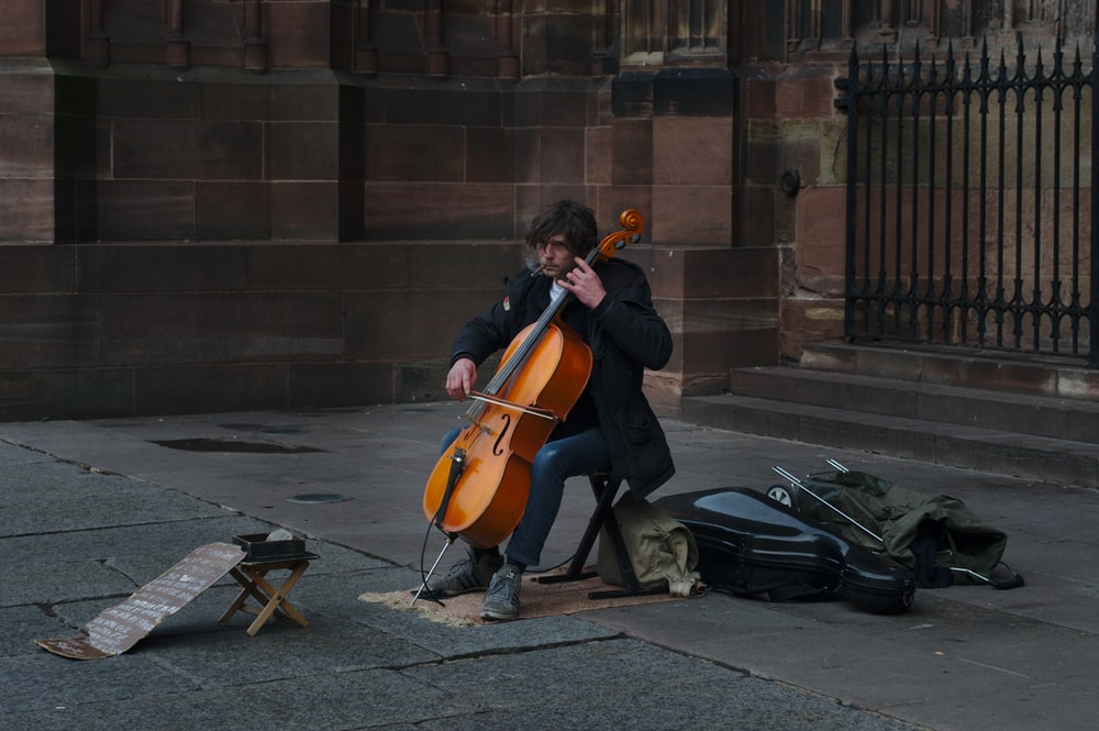 man playing cello near black gate