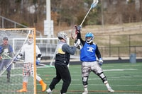 lacrosse players playing on field at daytime