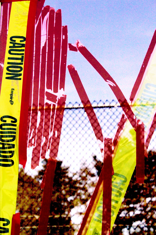 yellow Caution ribbon near metal fence