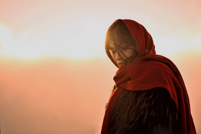 woman wearing red headscarf against the sun photo
