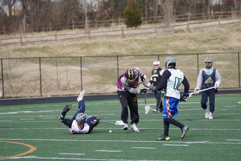 lacrosse players on field at daytime