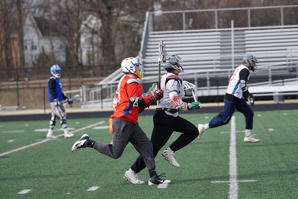 four men playing lacrosse game during daytime