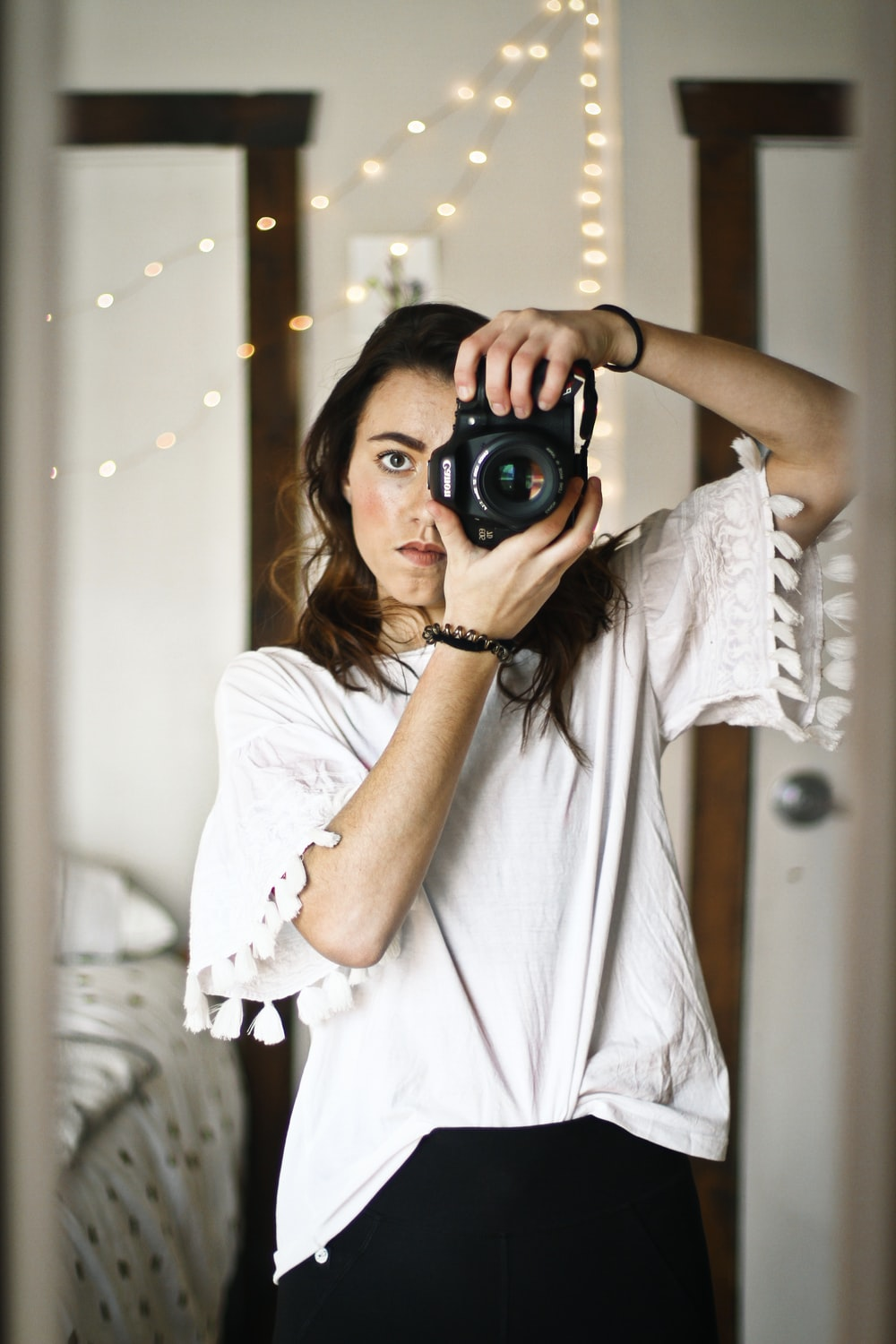 woman in white top looking through the camera peephole