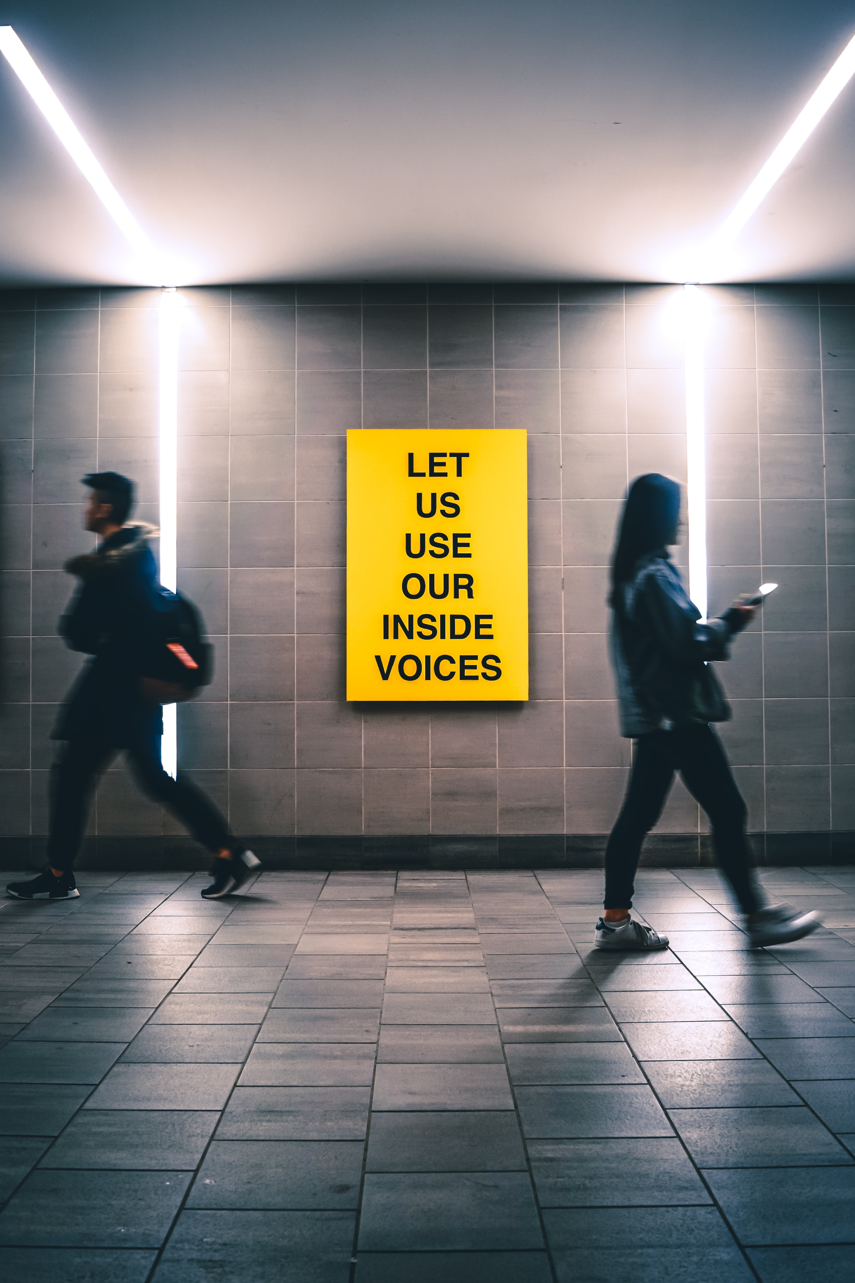man and woman walking inside building near Let us use our inside voices sign