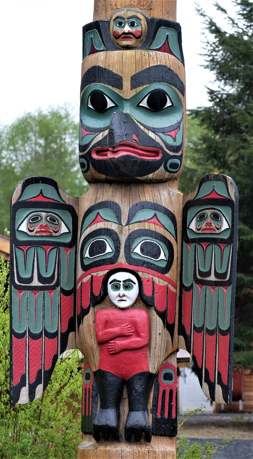 brown, red, and black totem pole near trees