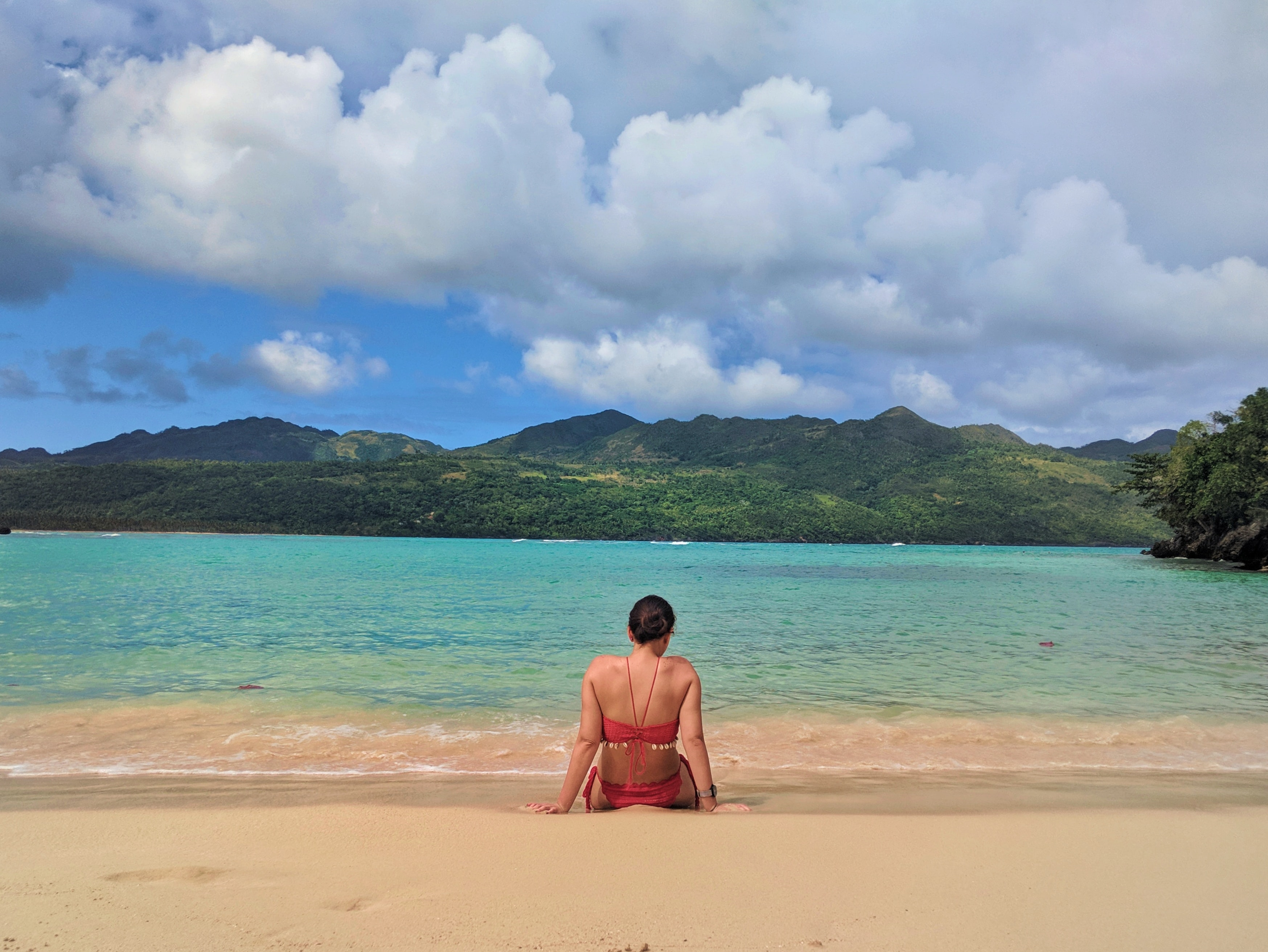 woman sitting near seashore viewing calm sea