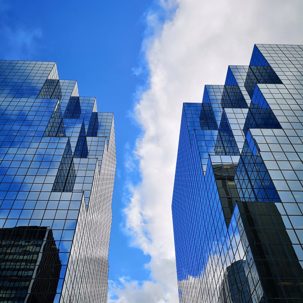 glass buildings under blue sky with clouds