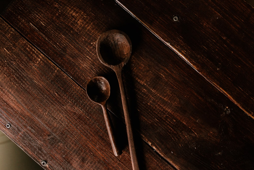 two brown wooden spoons on brown wooden table