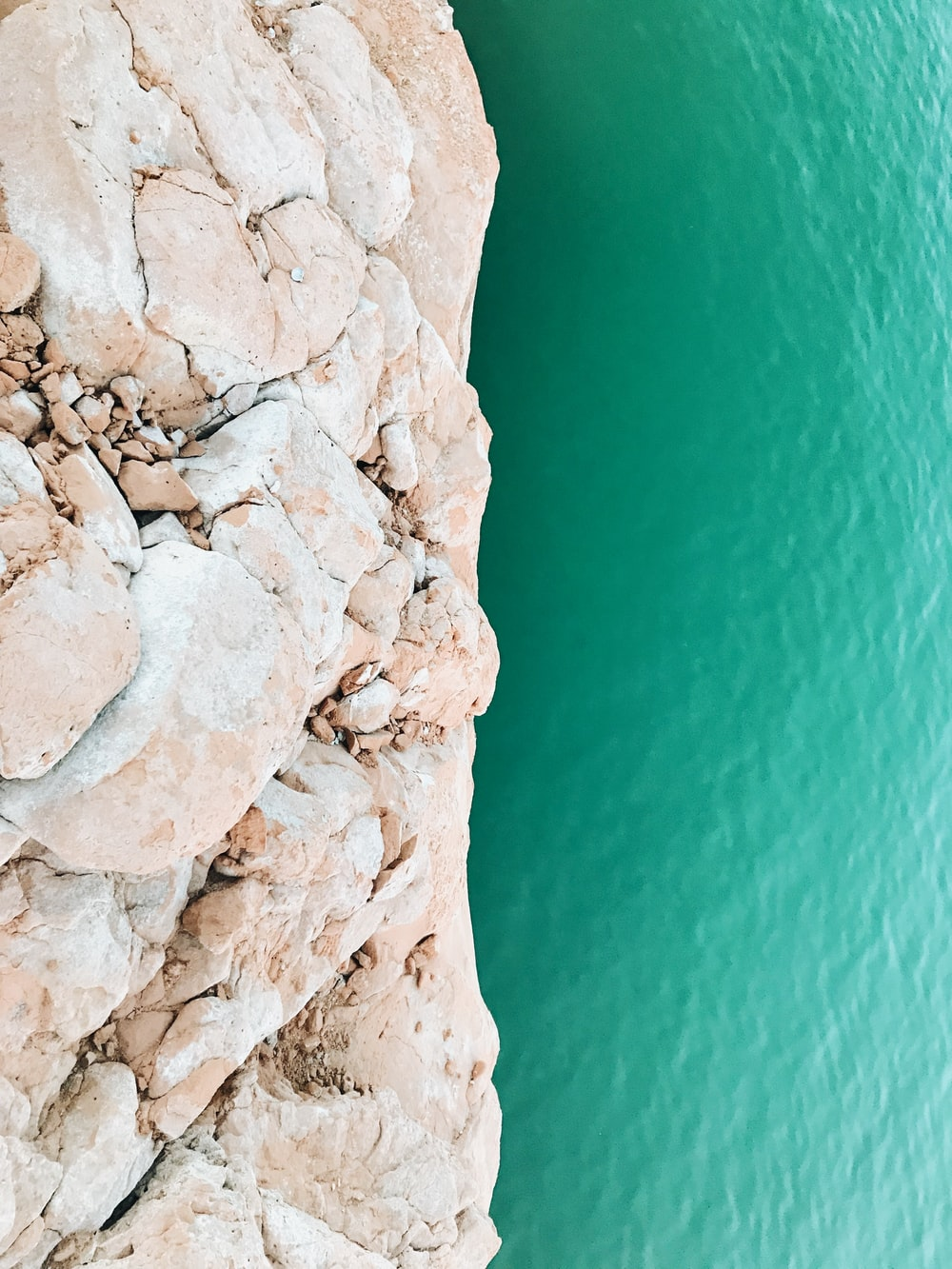 brown rock formation beside beach during daytime