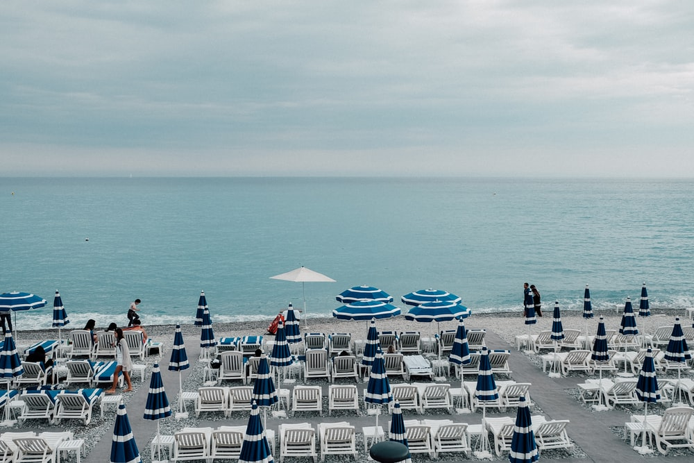 white lounger chair beside beach during daytime