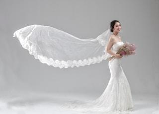 woman wearing white wedding dress holding flower bouquet