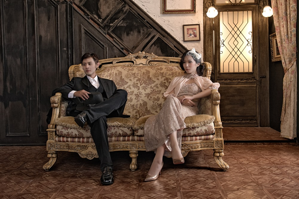 man and woman sitting on beige sofa