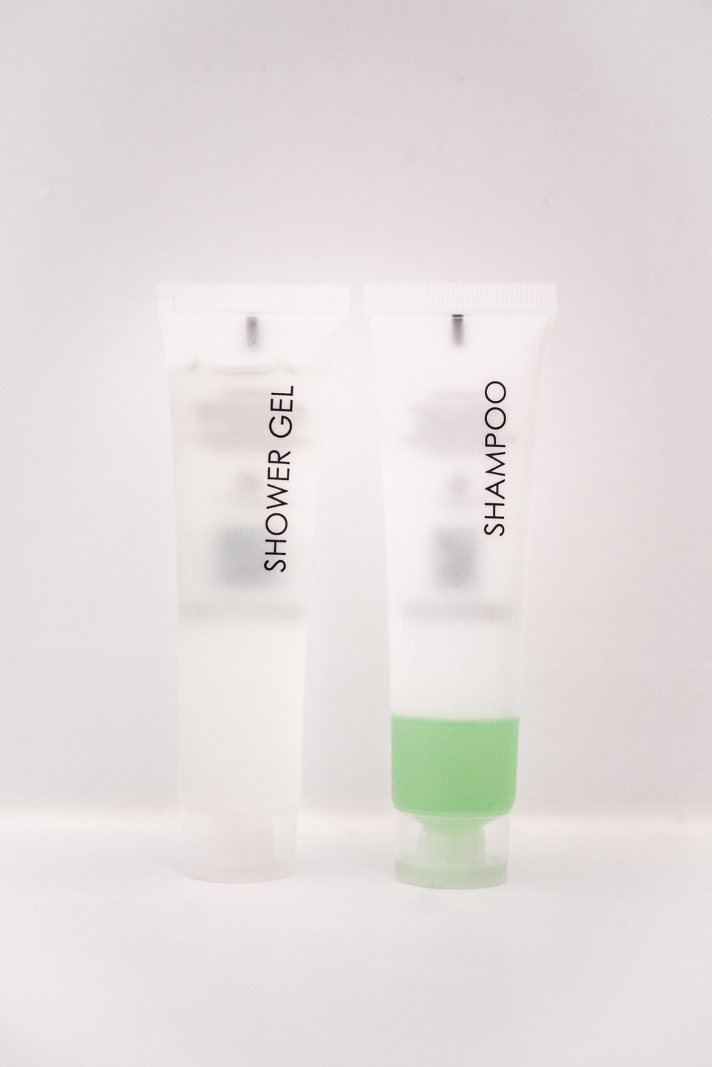 shower gel and shampoo soft-tube bottles on white surface