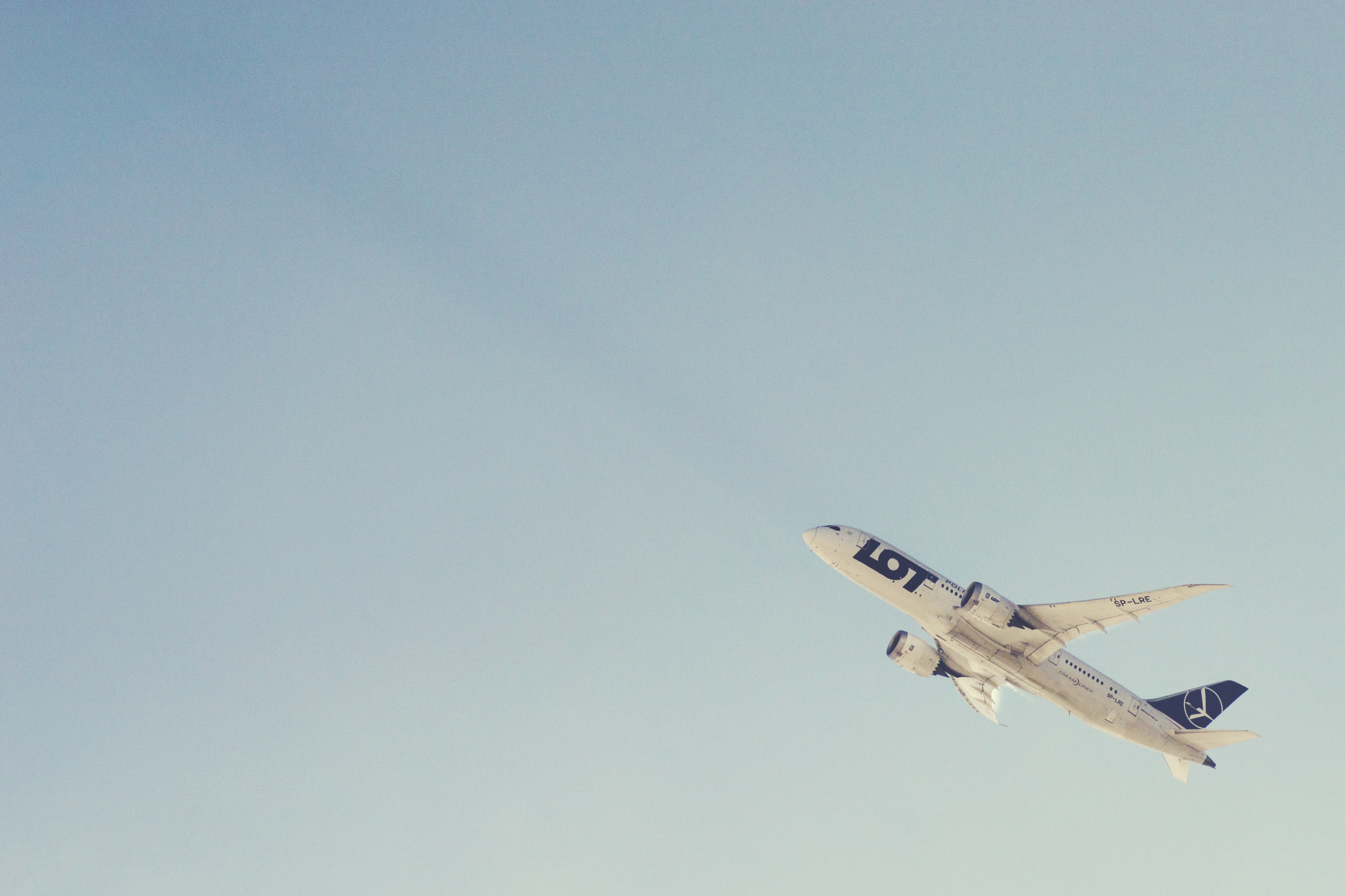 white passenger plane taking off through the sky