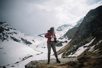 woman standing on rock near mountain covered with snow