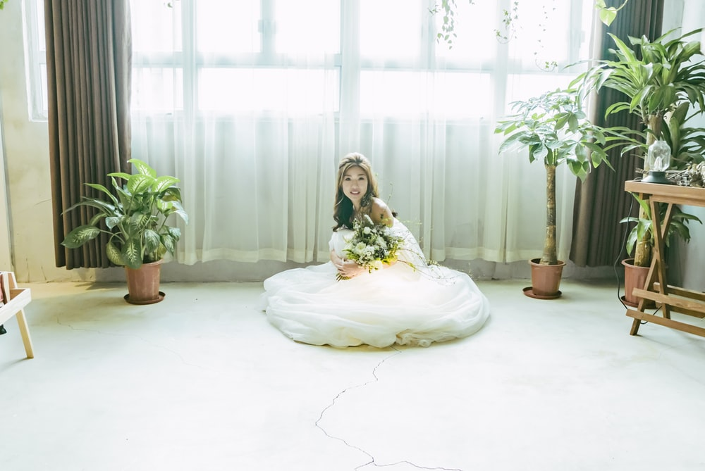woman wearing wedding dress sitting on floor
