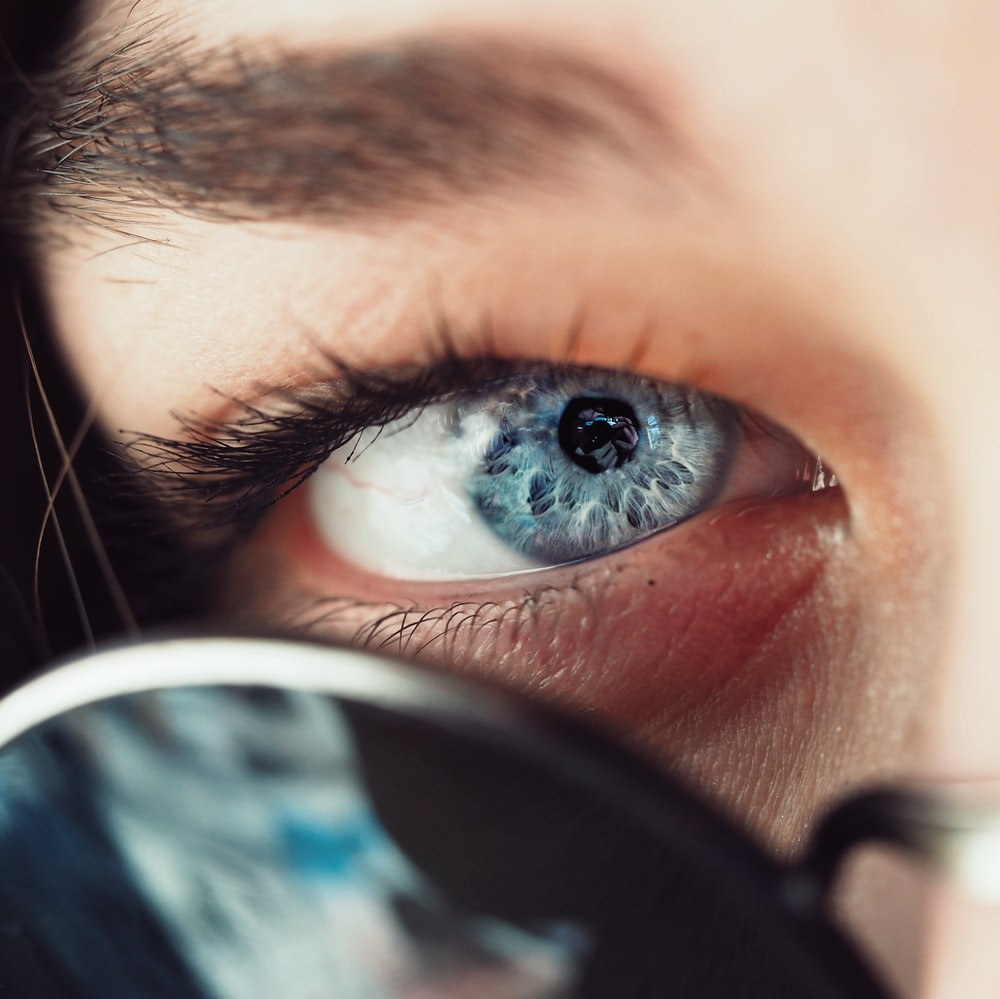 selective focus photo of person's eye iris and eye pupil