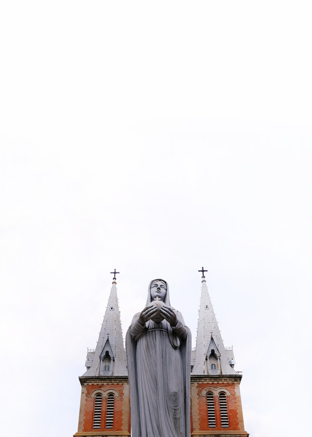 low-angle photography of religious sculpture outside cathedral during daytime