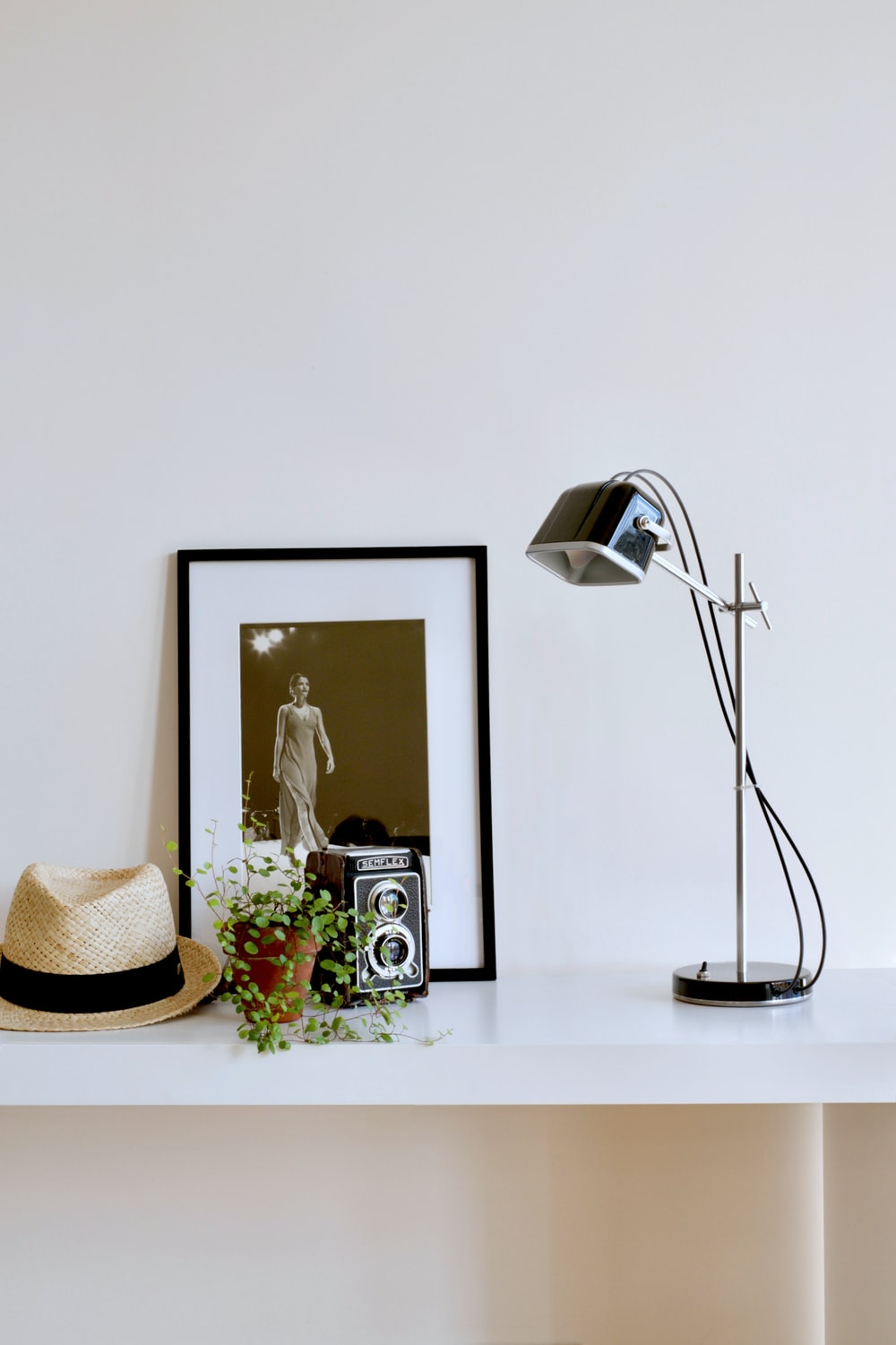 beige fedora hat, green vines and 8mm camera in front of photo on white desk