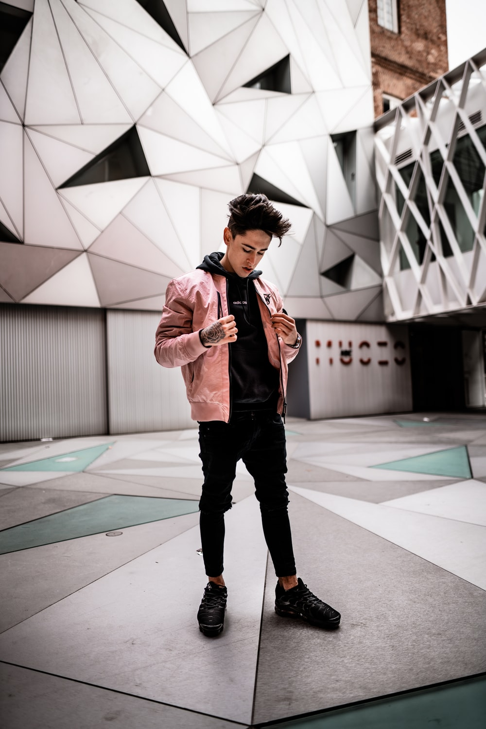 standing man wearing pink jacket looking down inside concrete building