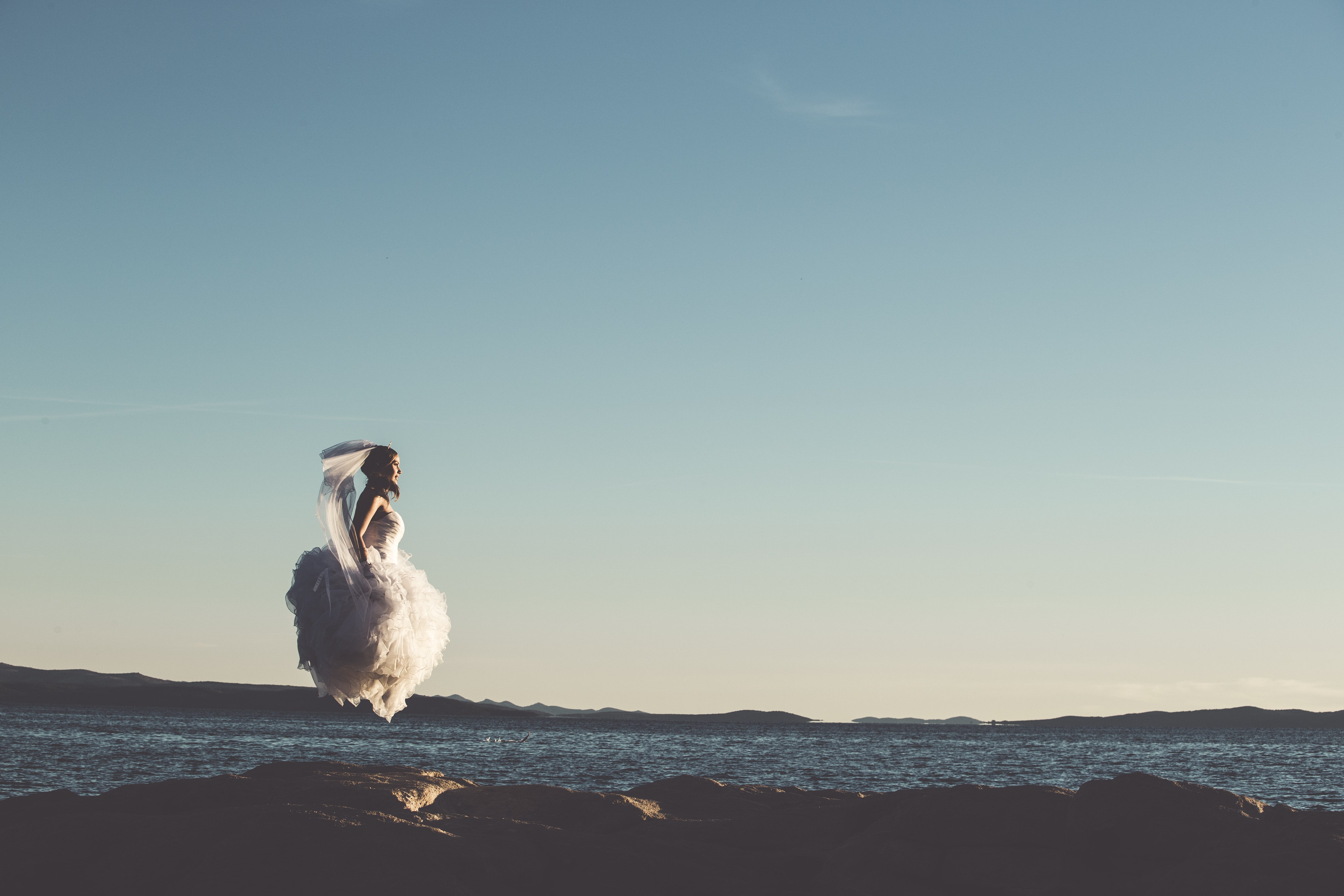 woman in white bridal gown jump in mid air next to body of water