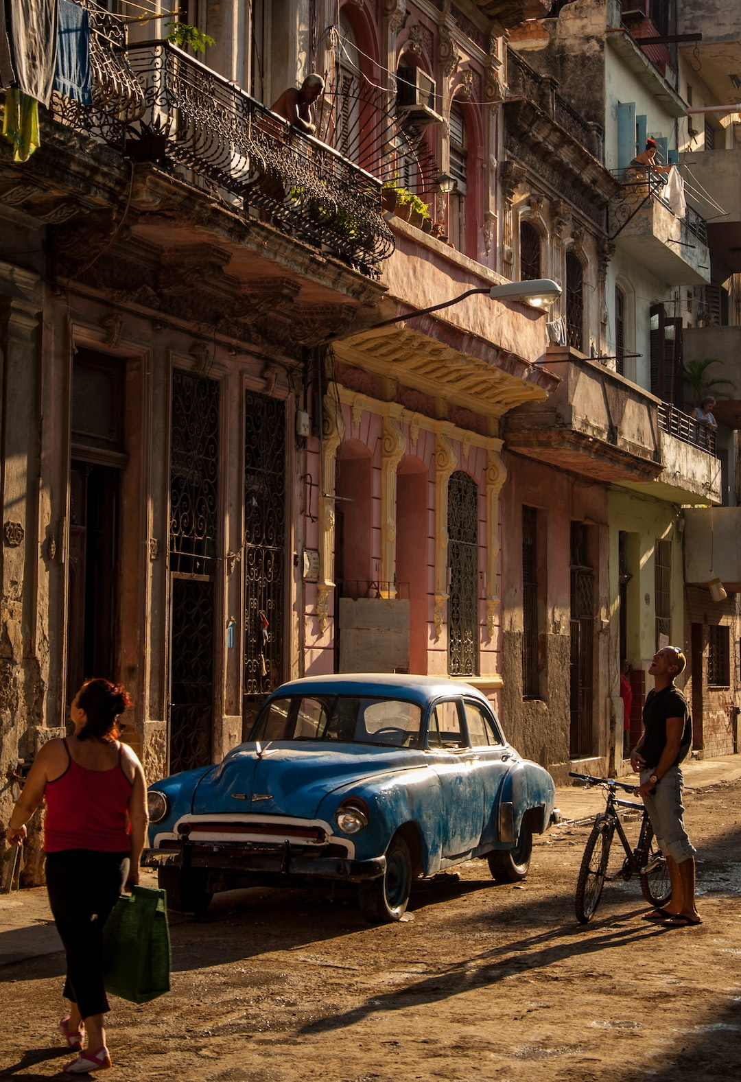 Locals, Architecture, Classic Car and Golden Light make up this travel stock image of Old Havana