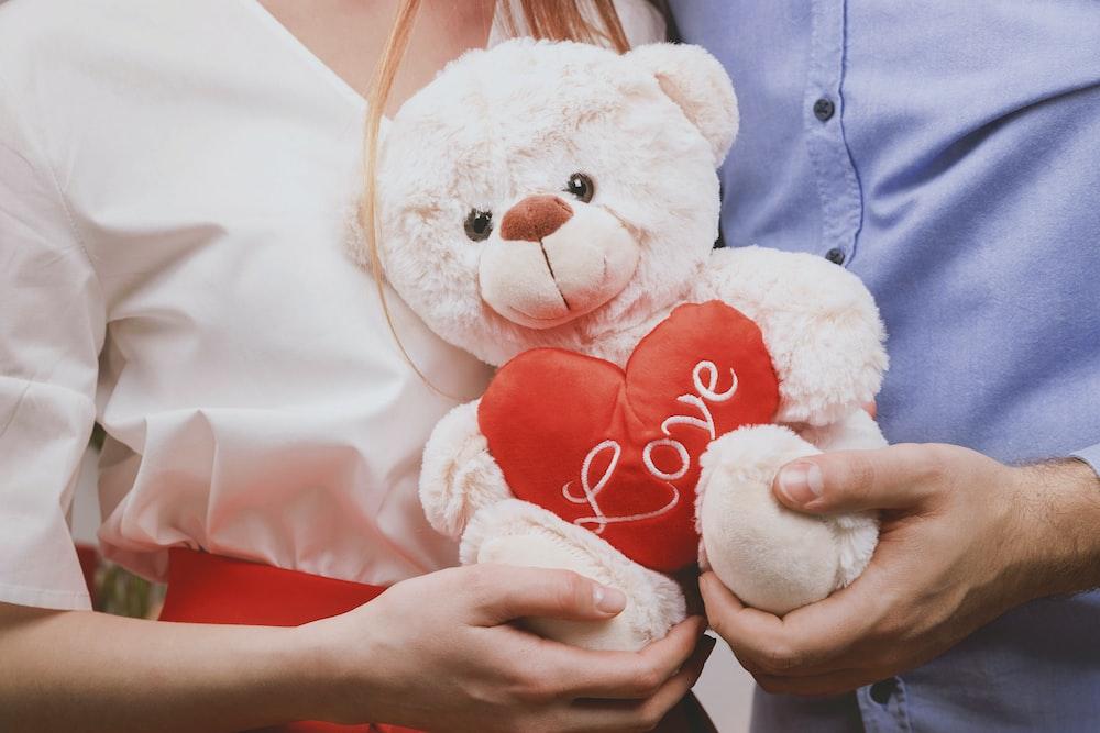 couple holding white bear plush toy