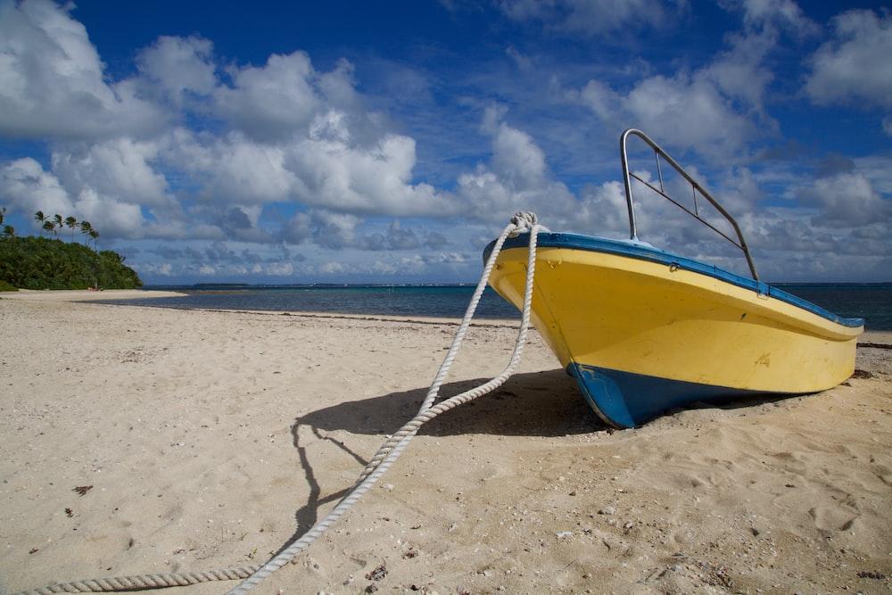 yellow and blue cuddy boat on seashore