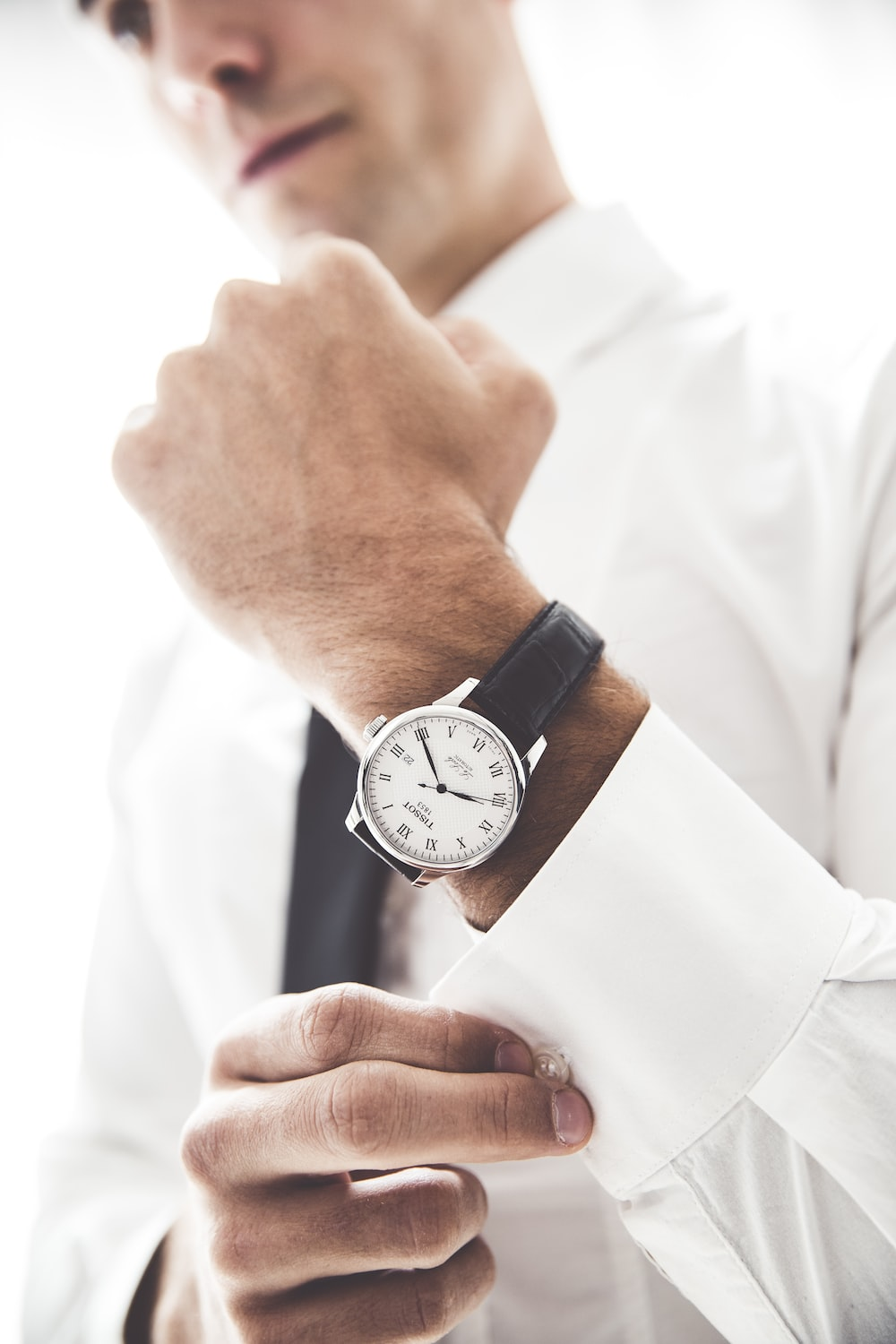person wearing round silver-colored analog watch with black leather band