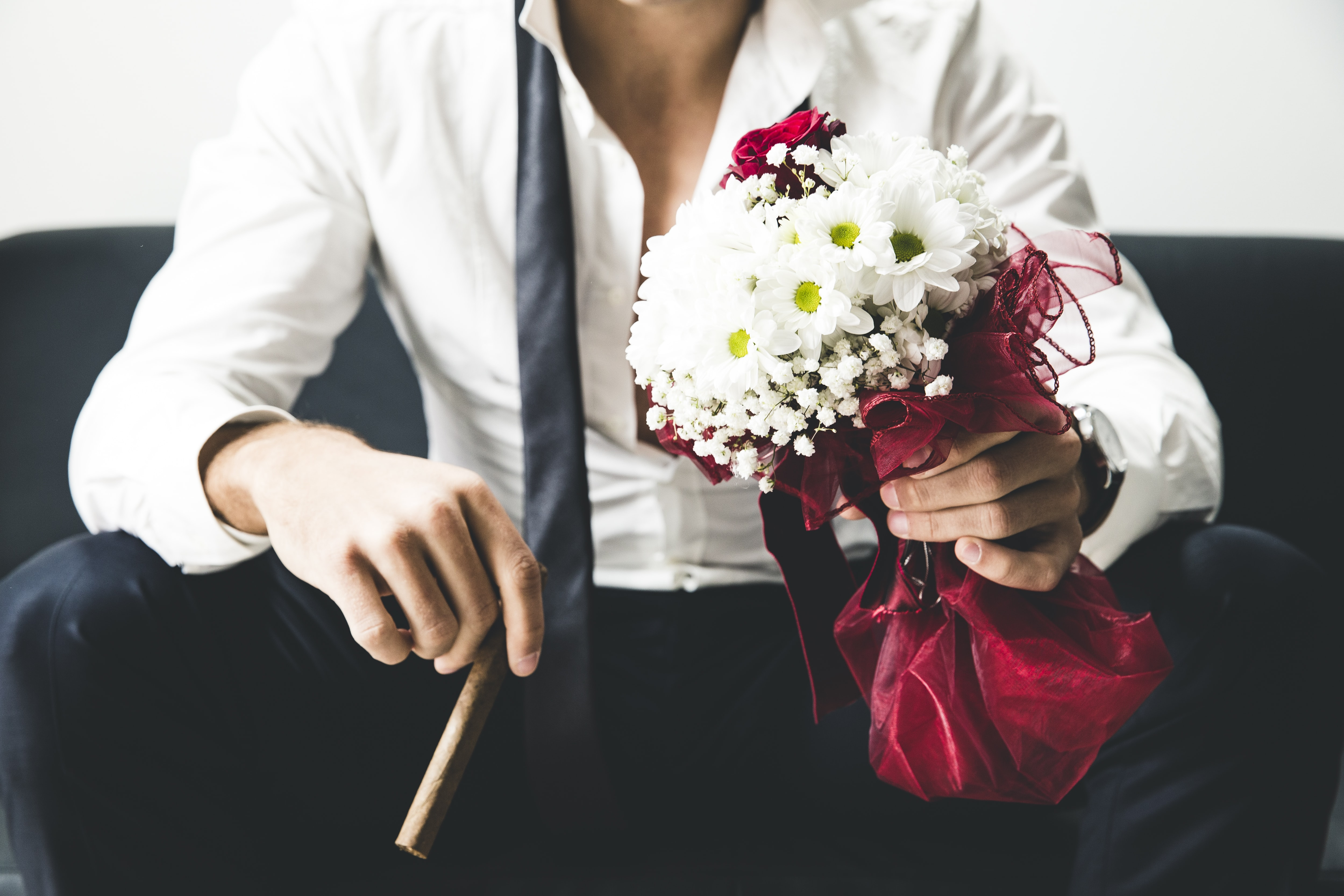 man holding bouquet of white flowers and brown tobacco
