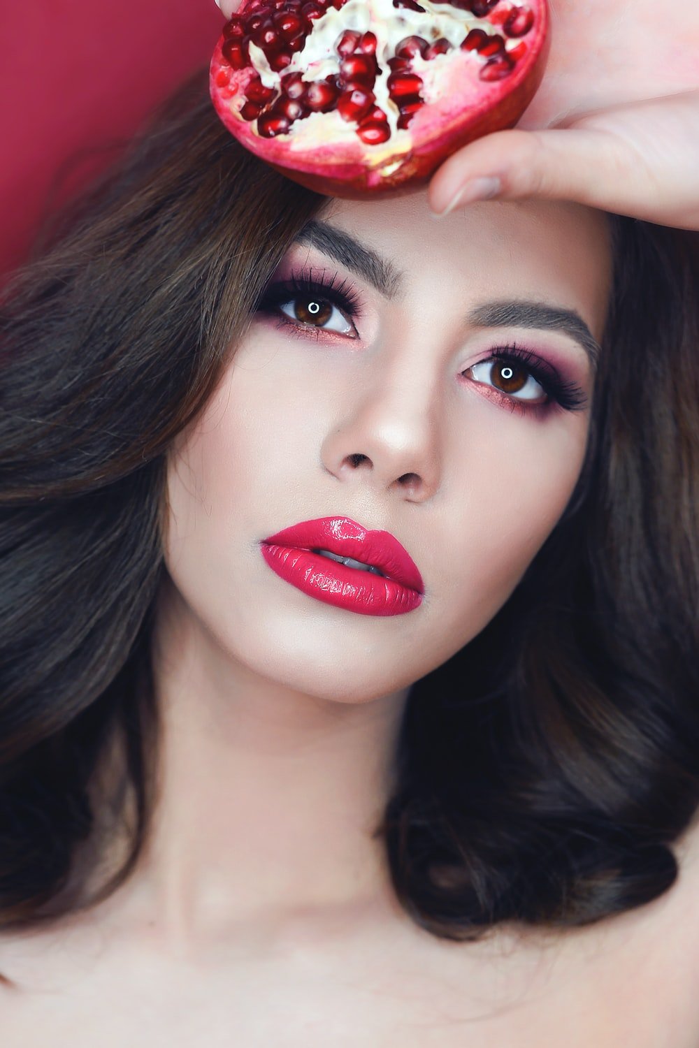 woman wearing makeup while holding sliced pomegranate fruit