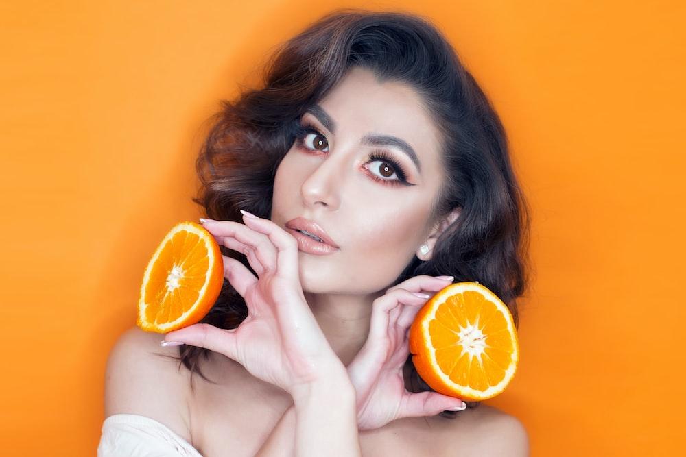 woman holding orange fruits